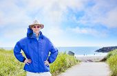 Caucasian Man In Forties Wearing Rain Jacket By Ocean Shore