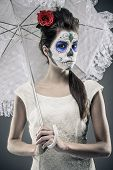 stock photo of day dead skull  - Day of the dead girl with sugar skull makeup holding lace umbrella - JPG