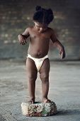 Naked african baby with diaper standing in rural poverty stricken area