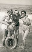 SOPOT, POLAND - CIRCA 1950: Vintage photo of man, two women and a girl with lifebuoy on beach, Sopot