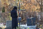 stock photo of headstones  - Woman in mourning clothes standing above headstone - JPG