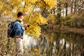 stock photo of fish pond  - Fisherman with spinning  - JPG