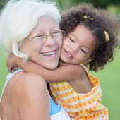 stock photo of grandmother  - Grandmother hugs her hispanic granddaughter on a park - JPG
