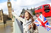 London - happy tourist holding British UK flag by Big Ben and red double decker bus. Excited girl si