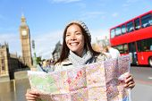 London tourist woman on Europe travel sightseeing holding map by Big Ben and red double decker bus. Tourism people concept with mixed race Asian girl smiling happy, Westminster Bridge, London, England