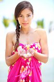 Beautiful serene woman on beach in sarong holding flower in palm of hands. Portrait of pretty gracef