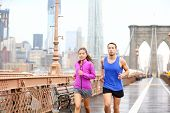 Running couple. Runners jogging outside in rain. Asian woman and Caucasian man runner and fitness sp