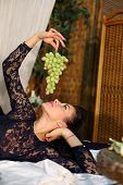 Beautiful woman lies on bed and holds bunch of green grapes in bedroom.
