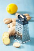 fresh ginger root and grater over blue