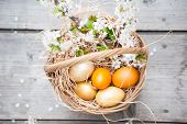 Easter holiday concept with yellow eggs in basket and cherry blossom flowers on wooden surf