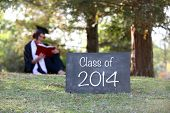 2014 graduate reading in cap and gown - shallow depth of field
