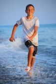 Teenager Boy Running In Wet Clothes On Beach