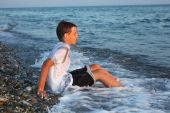 Sitting Teenager Boy In Wet Clothes On Stone Seacoast