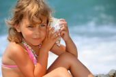 Pretty Little Girl Has Leant Seashell Bowl To An Ear On Seacoast
