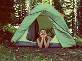 happy asian boy in camping tent in summer forest - vintage retro style