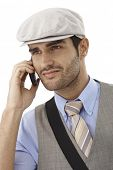 Portrait of young man talking on mobilephone, smiling, looking away, wearing hat.