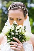 Closeup portrait of young bride peeking over bouquet in garden