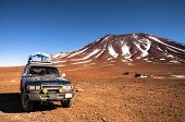 foto of four-wheel drive  - 4x4 offroad vehicle in the middle of peruvian highlands with mountain in background - JPG