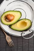 Halved Avocado On Vintage Plate. Closeup.
