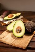 Many Halved Ripe Avocados On Wooden Background.