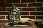 stock photo of kerosene lamp  - Burning kerosene lamp and books on brick wall background - JPG