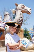 Boy in a pirate hat in amusement park.