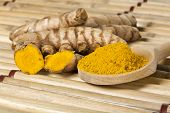 image of curcuma  - Ground turmeric on wooden spoon and turmeric roots on bamboo mat - JPG