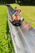 stock photo of luge  - Portrait of happy couple enjoying alpine coaster luge during summer - JPG