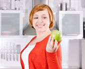 Redhead housewife with apple in home kitchen