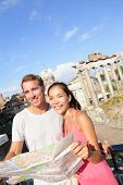 Tourists holding map by Roman Forum sightseeing on travel vacation in Rome, Italy. Happy tourist couple, man and woman traveling on holidays in Europe smiling happy. Interracial Asian Caucasian couple