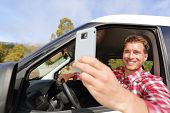 Driver taking photo with camera smartphone driving in car. Happy man taking picture with smart phone
