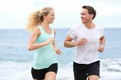 Running couple jogging exercising on beach talking and training as part of healthy lifestyle. Two fi