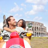 Rome couple on scooter by Colosseum, Italy. Romantic happy lovers driving scooter on honeymoon havin