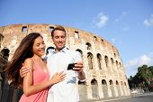 Couple in Rome by Colosseum using smart phone looking at pictures or using travel app in Italy. Happ