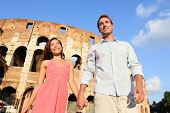 Couple in Rome by Colosseum walking holding hands in Italy. Happy lovers on honeymoon sightseeing ha