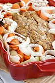 stock photo of meatloaf  - Casserole dish of freshly prepared meatloaf with onions carrots and potatoes - JPG