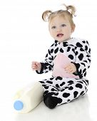 An adorable baby girl happy in her holstein cow costume, sitting by a bottle of milk.  On a white ba