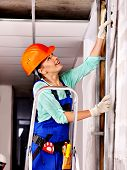 Happy woman in builder uniform indoor.