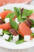 stock photo of pecan  - Spinach grapefruit goat cheese salad with pecan nut on white plate