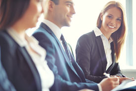 foto of seminar  - Smiling businesswoman looking at camera at seminar with her colleagues near by - JPG