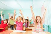 Happy kids with arms up sit in classroom rows