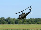 picture of military helicopter  - Camouflage green military helicopter flying over a field - JPG