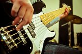 image of studio  - a musician playing a bass guitar in studio - JPG