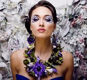 floral face art with anemone in jewelry, sensual young brunette woman