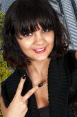 foto of gang  - Beautiful young woman flashing a gang sign with her hand - JPG