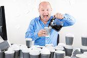 Happy businessman drinks way too much coffee