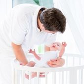 Happy Young Father Putting His Newborn Baby In A White Crib At A Big Window