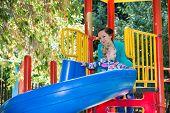 Happy Adorable Girl With Mom On Children's Slide On Playground Near Kindergarten Montessori On Summe