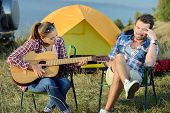 stock photo of serenade  - Cute woman serenading her men on camping trip on a sunny day - JPG