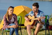 image of serenade  - Cute man serenading his girlfriend on camping trip on a sunny day - JPG